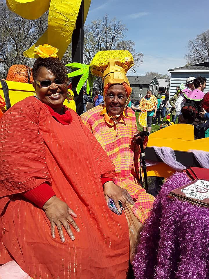 Two zAmya Troupe Members sitting on a float in the May Day Parade. They are dressed in bright reds and yellows.